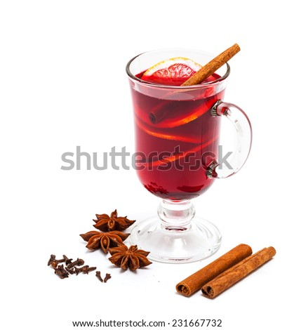Hot red mulled wine with orange slice, anise and cinnamon sticks isolated on white background. - stock photo
