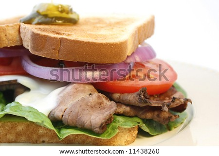 Hot roast beef sandwich with melted cheese, lettuce, tomato, and red onion on a plate with white background - stock photo