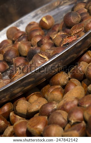 Hot Roasted chestnuts on market stall. - stock photo