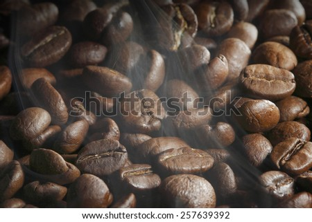 Hot roasted coffee beans and steam