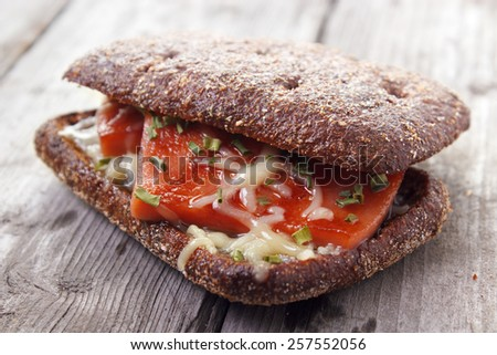 Hot rye bread sandwich with grilled sausage and cheese on gray wooden surface - stock photo