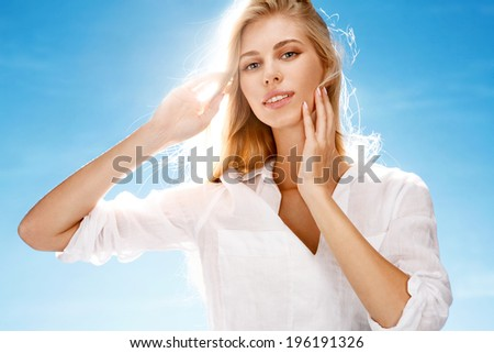 Hot season / portrait of happy girl styling her hair on blue background