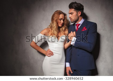 hot sexy elegant man holds his woman's hand, he is looking at her while she looks down, in studio - stock photo