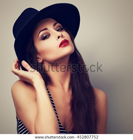 Hot sexy female model with bright makeup and red lipstick in black hat posing. Toned vintage portrait