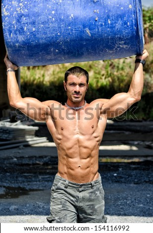 Hot, shirtless, muscular construction worker carrying big barrel over his head - stock photo