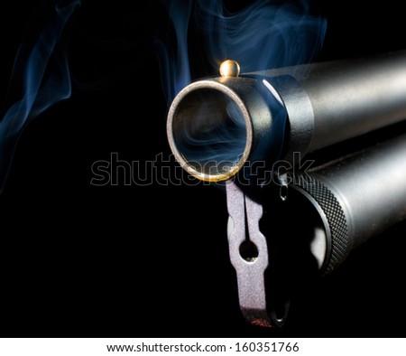 Hot shotgun that has smoke around the muzzle - stock photo