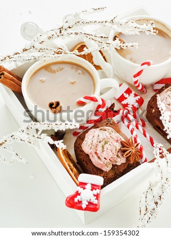 Hot spiced cocoa with milk and chocolate brownies with coconut, red grape whipped cream and mattya. Shallow dof.