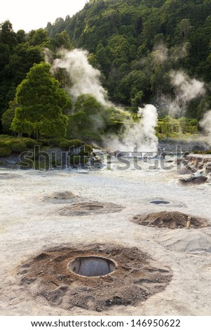 Hot springs and cooking holes at the edge of Lagoa das Furnas. - stock photo