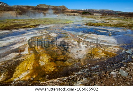 Hot Springs:  Mineral water emerges at near boiling temperatures and flows across colorful mud plains in an area of geothermal activity in southern Iceland. - stock photo