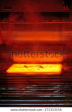 hot steel plate on conveyor - stock photo