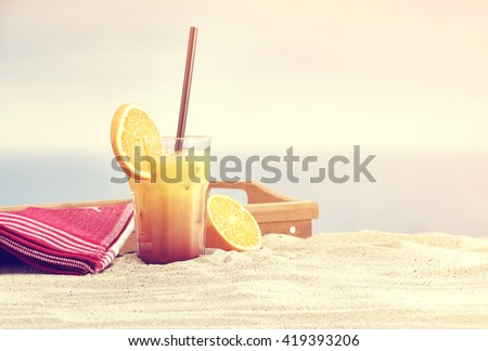 hot summer day and orange drink with ice on hot sand