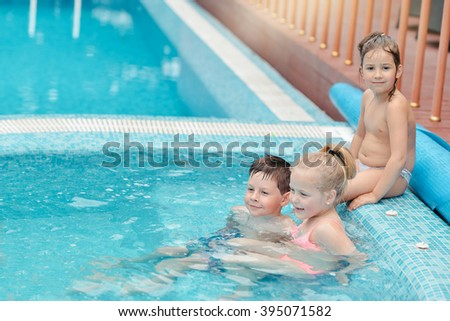 hot summer day little children playing in the azure pool - stock photo