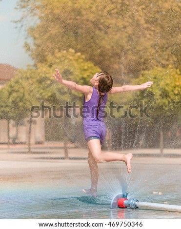 Hot summer in the city - girl is running through fountain