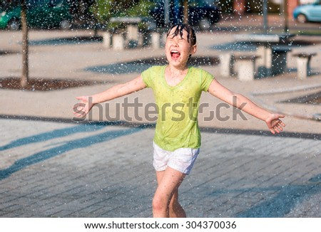 Hot summer in the city - girl is running through fountains - stock photo