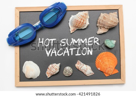 Hot Summer Vacation text on chalk board with swimming goggle and shell - vacation and business concept - stock photo