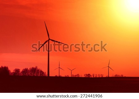 Hot sun and red sky over windmills. Alternative energy concept. - stock photo