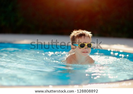 hot sunny day, the boy with sunglasses floating in the pool - stock photo