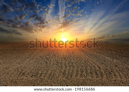 Hot sunset over ploughed field  - stock photo