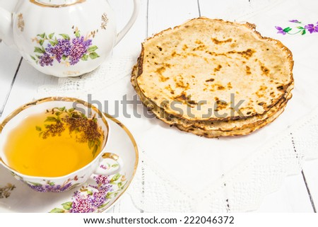 Hot tasty baked russian pancakes with tea in an antique thin porcelain painted cup and teapot on a white wooden background with lace cotton napkin. Holiday table for Shrovetide. Delicious breakfast  - stock photo