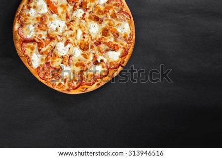 Hot tasty delicious rustic homemade american pizza with salami hamon mozzarella with thick crust on black table - stock photo