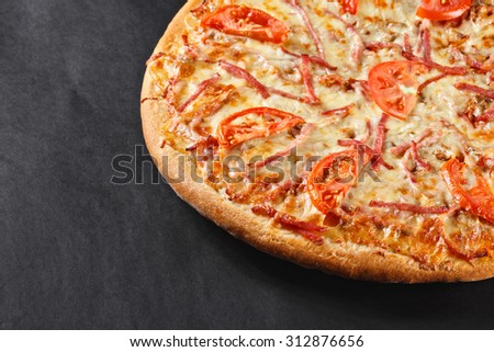 hot tasty delicious rustic homemade american pizza with tomato, meat,  with thick crust on black table - stock photo