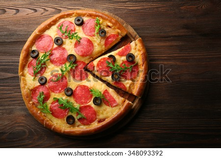 Hot tasty pizza with salami and olives on wooden background