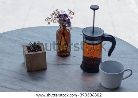Hot tea a press, a white mug on a white table and a vase with a flower