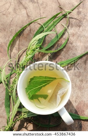 Hot tea and hemp, cannabis on the wooden background - stock photo