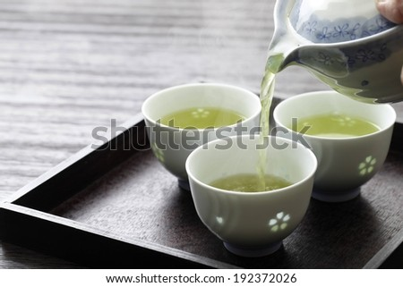 Hot tea being poured into a white cup. - stock photo