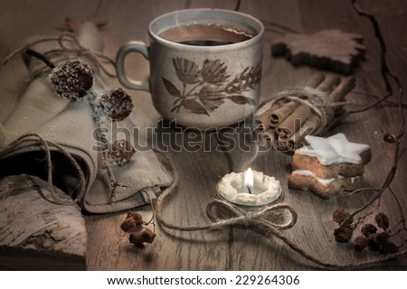 Hot tea, burning candle and Christmas cookies on decorated table, toned image - stock photo