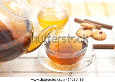 Hot tea flowing from teapot into glass mug