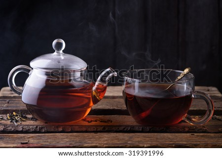 Hot tea in glass teapot and cup with spoon and steam on wooden table dark still life - stock photo