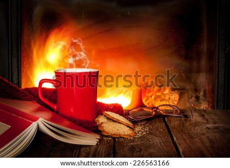 Hot tea or coffee in a red mug, ginger cookies, book and glasses on vintage wood table. Fireplace as background. Christmas or winter warming drink. Layout with free text space. - stock photo