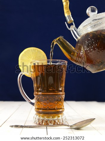 Hot tea with lemon, still life with glass kitchenware and silver spoon on blue background - stock photo
