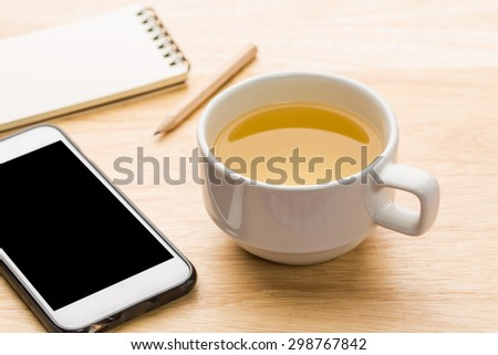 Hot tea with smartphone and notebook on office table.