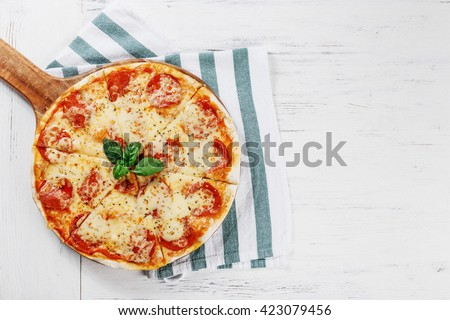 Hot true PEPPERONI ITALIAN PIZZA on towel with salami and cheese. TOP VIEW Tasty traditional pepperoni pizza on board on white wooden table. Copy space for your logo. Ideal for commercial  - stock photo
