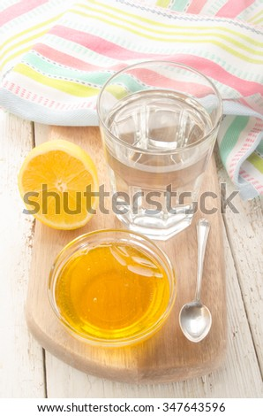 hot water in a glass on wooden board with lemon, honey and spoon - stock photo