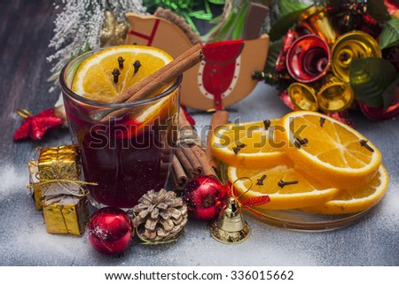 Hot wine (mulled wine) with spices on wooden background. Selective focus.