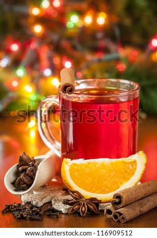 Hot winter drink with spices and orange. - stock photo
