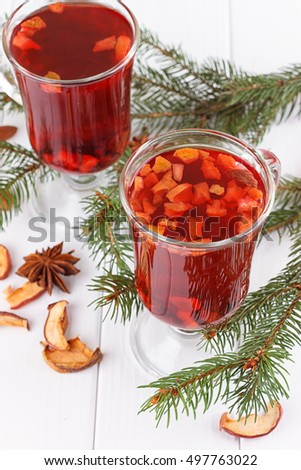 Hot winter drinks. Red tea , cinnamon, star anise seeds by fir needles
