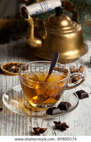 Hot winter tea with dark chocolate and old vintage teapot on old wooden table - stock photo