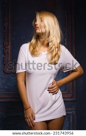 Hot young woman in white t-shirt and panties posing in gothic interior - stock photo