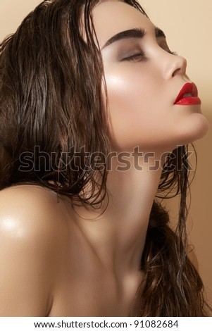 Hot young woman model with sexy bright red lips makeup, strong eyebrows, clean shiny skin and wet hairstyle. Beautiful fashion portrait of glamour female face - stock photo
