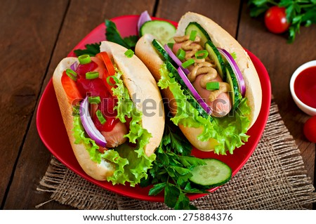 Hotdog with ketchup, mustard, lettuce and vegetables on wooden table - stock photo