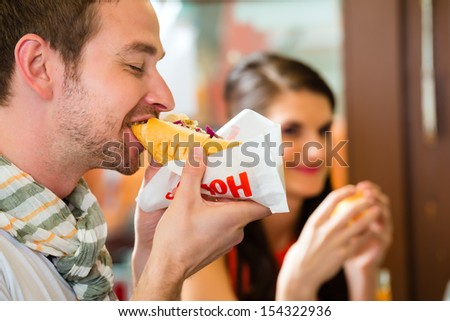 Hotdog - young customers in a snack bar eating delicious fast food sausages - stock photo
