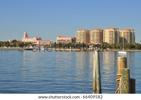 Hotel and condos on the shoreline of an inlet seen from across the harbor. Sailboat seen heading out  to the bay amidst the serene reflections of the buildings on a peaceful morning. - stock photo