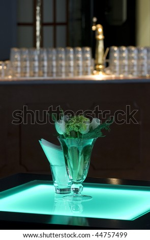 Hotel ballroom with luminous bar tables and a bar unit setup for a fancy reception. - stock photo