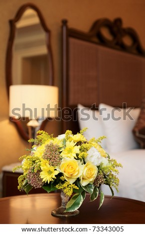 Hotel bedroom arranged with bunch of yellow flowers