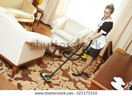 Hotel cleaning service. female housekeeping worker with vacuum cleaner in room apartment - stock photo