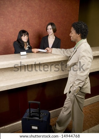 Hotel employees cheerfully welcome a guest. - stock photo